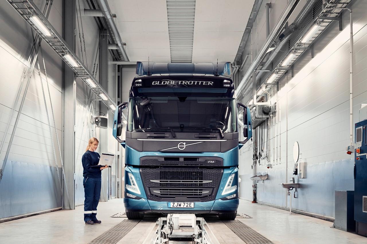 Een servicemonteur van Volvo met een laptop in haar hand staat naast een voertuig