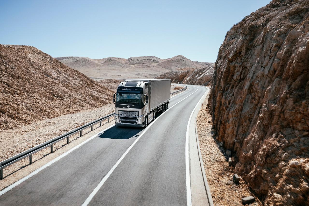 Een voertuig rijdt door een bergachtig woestijnlandschap