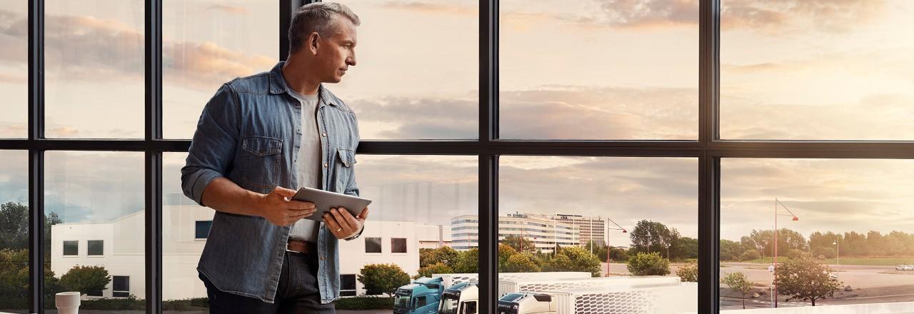 Een man met een tablet staat bij een raam en kijkt neer over zijn wagenpark